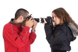 Young man and woman taking pictures of each other in front of the white background